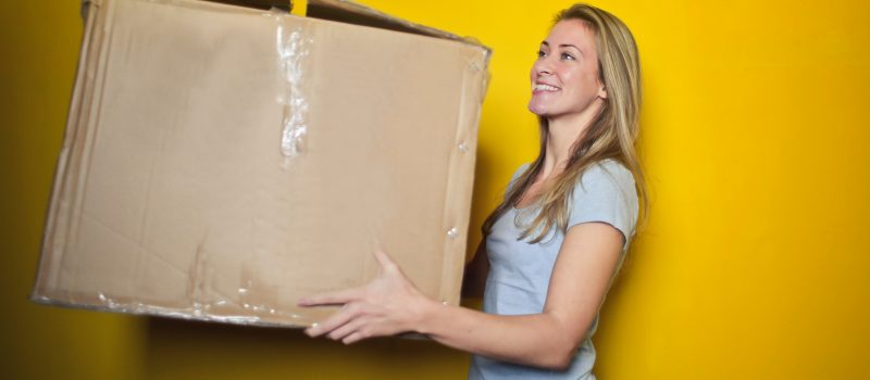 Female holding a large cardboard moving box